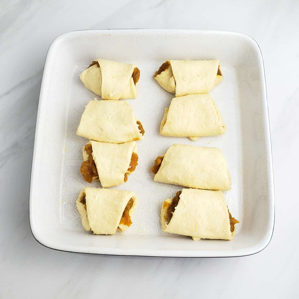 Unbaked crescent roll dough filled with pumpkin filling