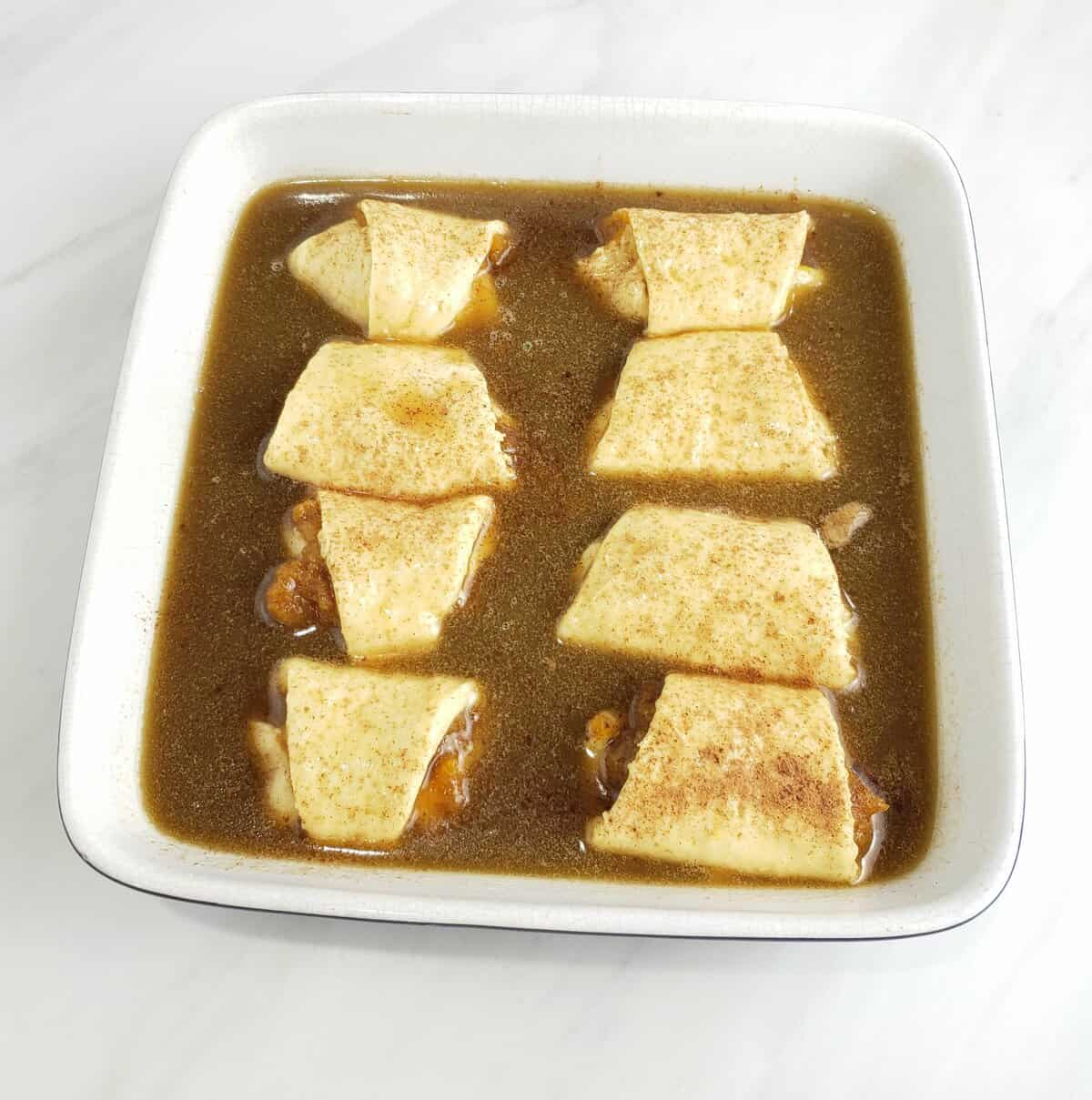 Unbaked crescent roll dough filled with pumpkin filling and brown sugar sauce in square dish