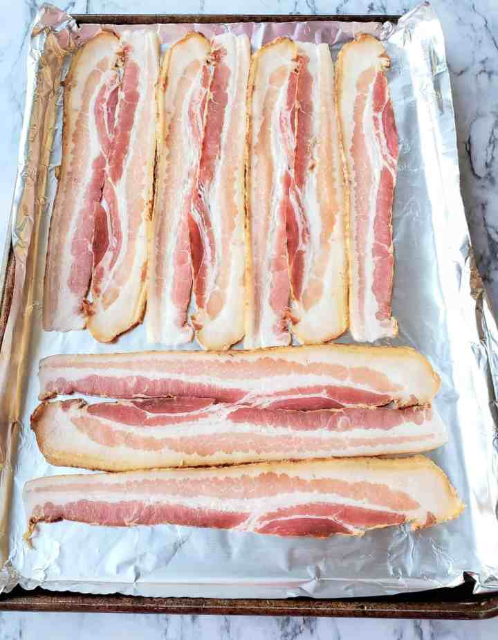 Thick cut bacon on a foiled line sheet pan