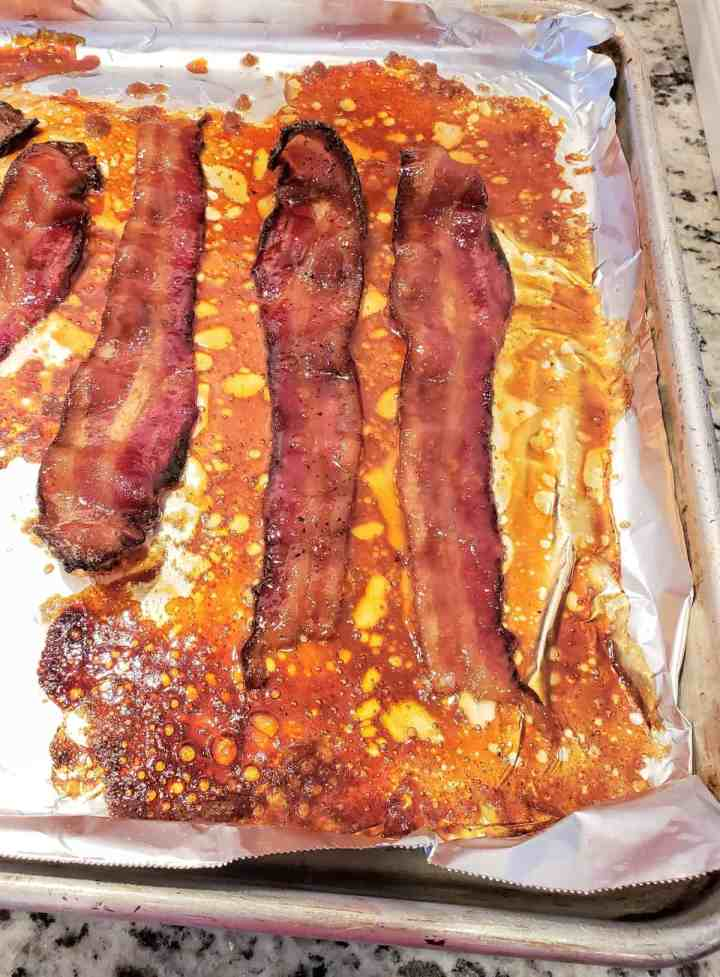 Slices of bacon candied on a foil lined sheet pan