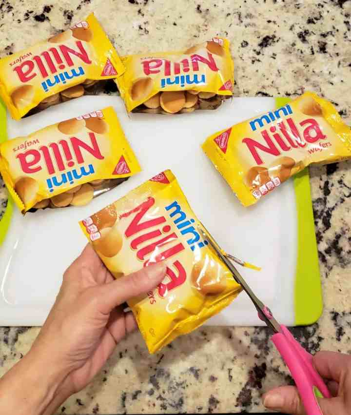Cutting vanilla wafer cookie packages open with scissors