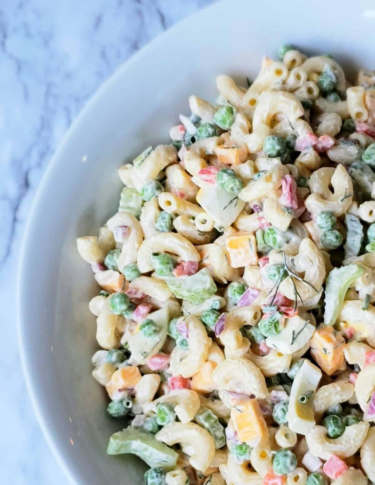 Close up edge of white bowl of macaroni salad on marble surface