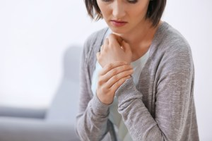 woman holding her wrist due to wrist pain