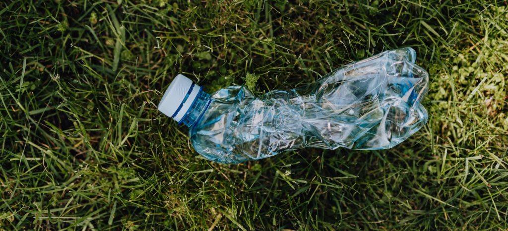 plastic flesje op het gras