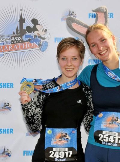 Finisherfoto van de halve marathon in Disneyland Parijs met de medailles voor het finisherscherm.