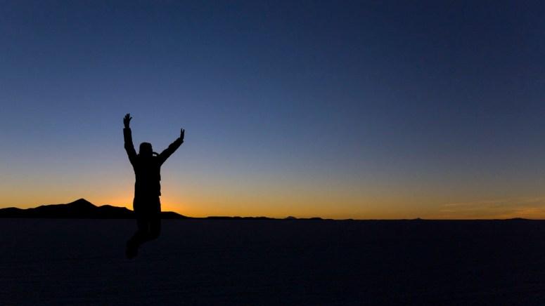 Iemand springt in de lucht tijdens de Zonsondergang op Salar de Uyuni