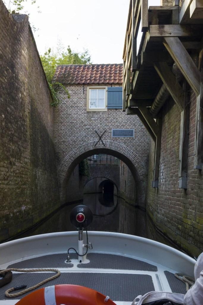 Een brug in Den Bosch gezien vanaf de Binnendieze. Je kunt over de Binnendieze varen met een bootje met gids.