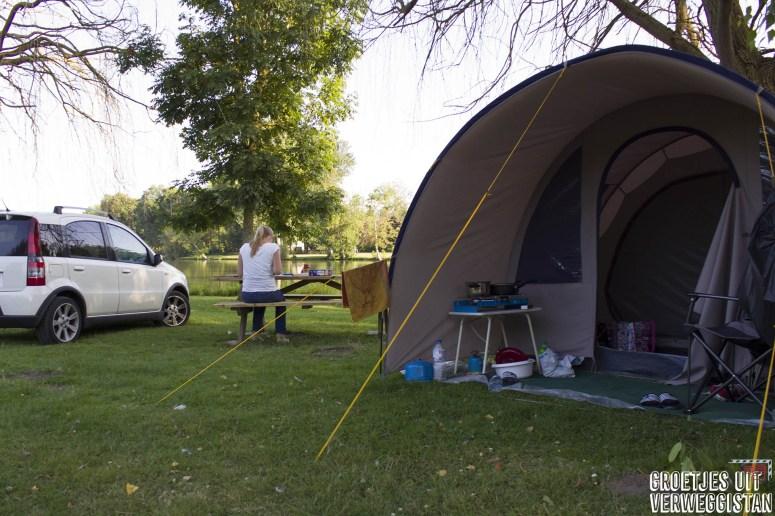 Kampeerplek aan het water met tent, auto en picknicktafel in Frankrijk