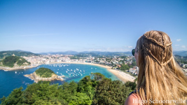 Uitkijkend over de baai van San Sebastián met helderblauw water en zon: meisje met blonde vlechten.