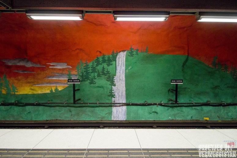 Metrokunst in Stockholm in metrostation Solna Centrum: oranjerode lucht en een landschap in het groen op de muren van het metroplatform.