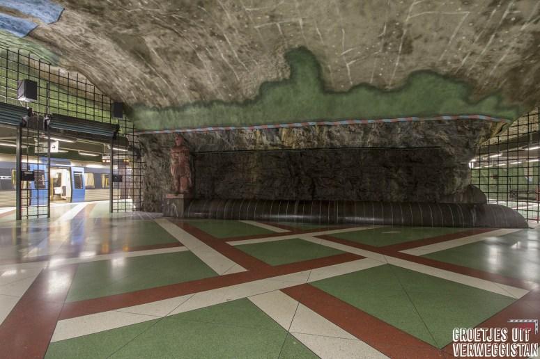 Metrostation Kungsträdgården in Stockholm, met beelden, gekleurde muren in groen, grijs en blauw en een vloer met een patroon in groen, wit en rood.