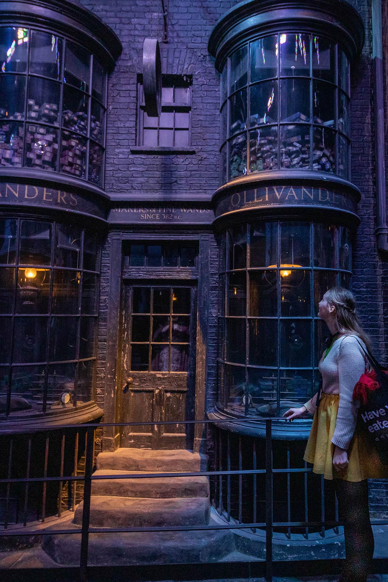 Meisje kijkt naar de etalage van de winkel Ollivanders op Diagon Alley in de Warner Bros Studio Tour