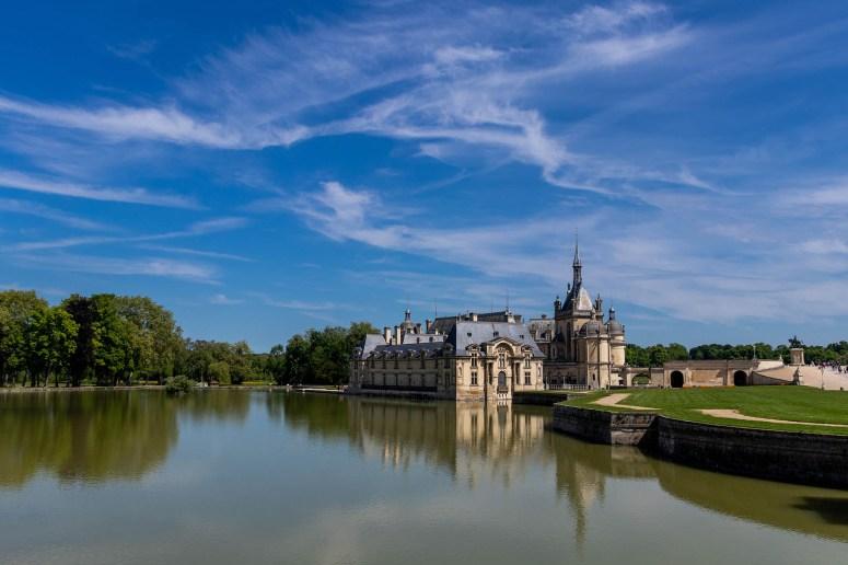 Kasteel van Chantilly met het water ervoor en een blauwe wolkenlucht