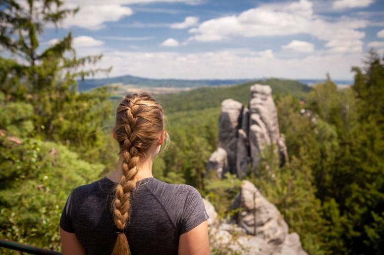 Meisje kijkt uit over Prachov Rocks in Český Ráj of het Boheems Paradijs in Tsjechië in de zon