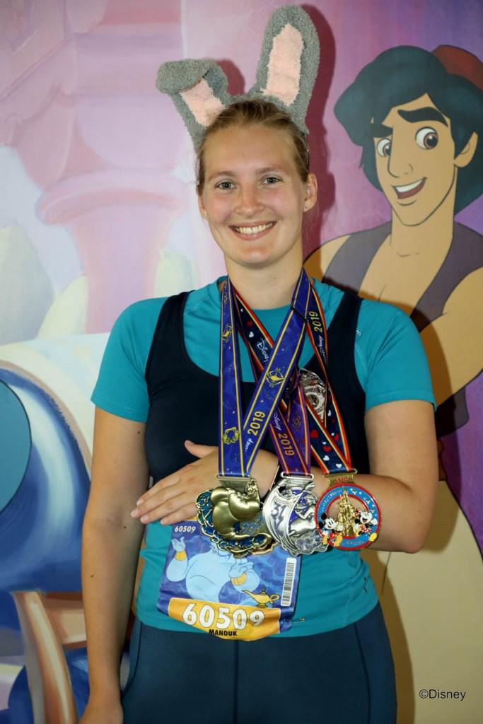 Meisje met 3 medailles voor de 36 kilometer challenge in Disneyland Paris na afloop van de halve marathon.
