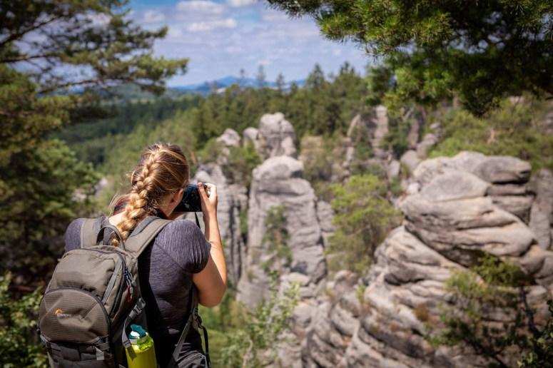Meisje met vlecht maakt foto van de rotsen van Prachov in het Boheems Paradijs.