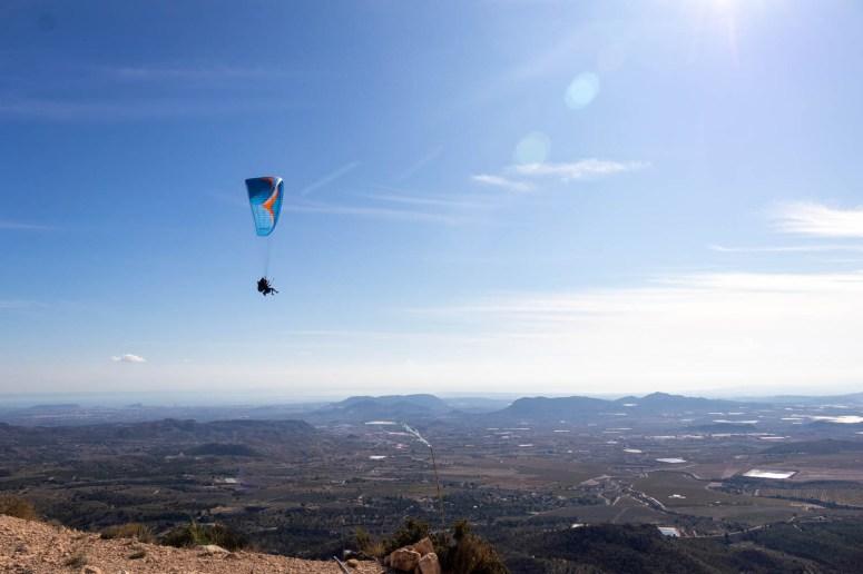 Blauwe paraglider hoog boven de horizon met Alicante op de achtergrond.