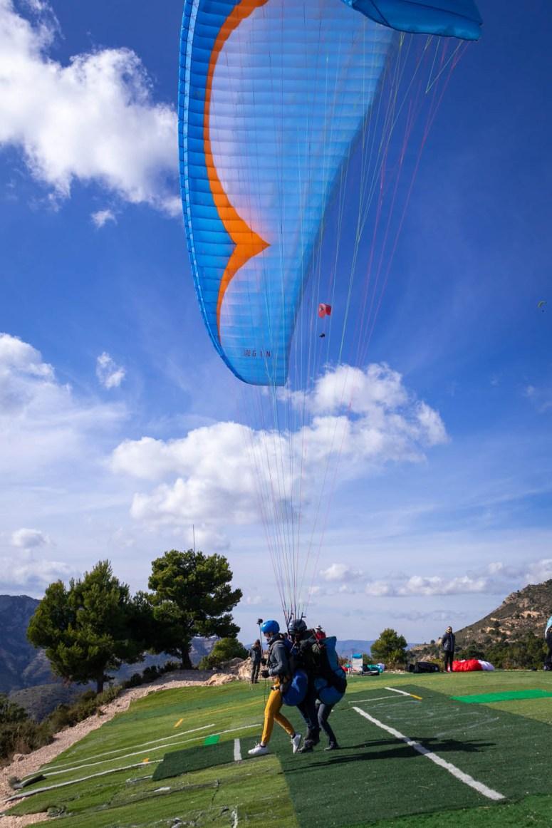 Manouk en piloot Juan rennen de berg af met de parachute al in de lucht.