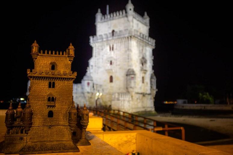 Torre de Belém, goed verlicht in het donker. Op de voorgrond een klein model van de toren, zodat je kan voelen hoe hij eruit ziet.
