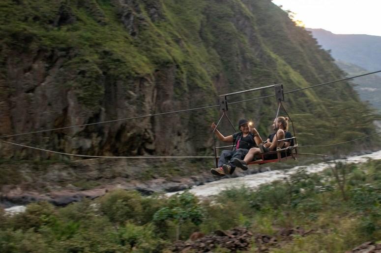 Handkabelbaan tijdens de Inka Jungle Trek: twee mensen zitten op een plateautje, dat een local met de hand naar de overkant trekt.