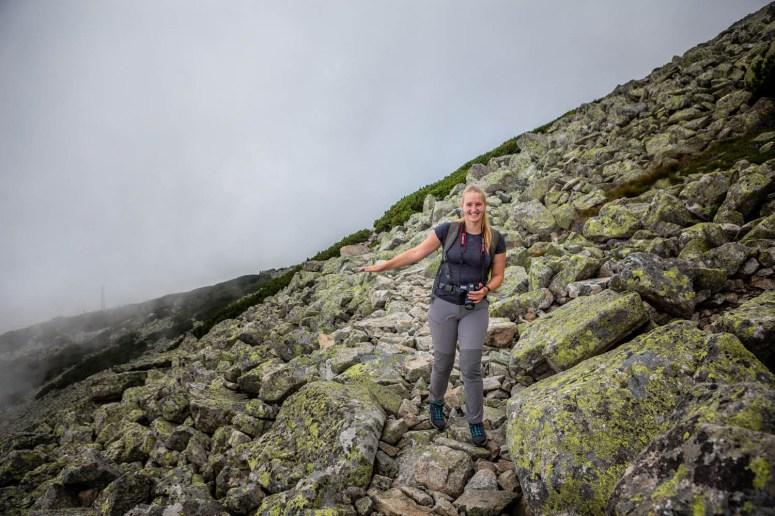 Manouk loopt over een pad van rotsen richting Zelene Pleso in het Tatragebergte in Slowakije.