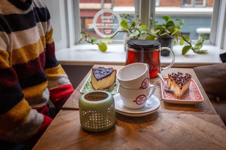 Cheesecakes en thee op een tafel bij Bertels Salon in Kopenhagen