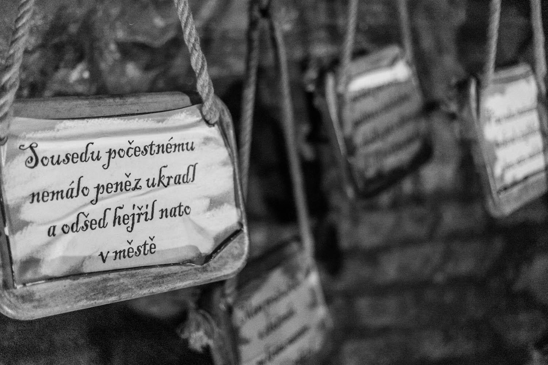 Zwartwit foto van bordjes die hangen in het ondergronds labyrinth in Brno