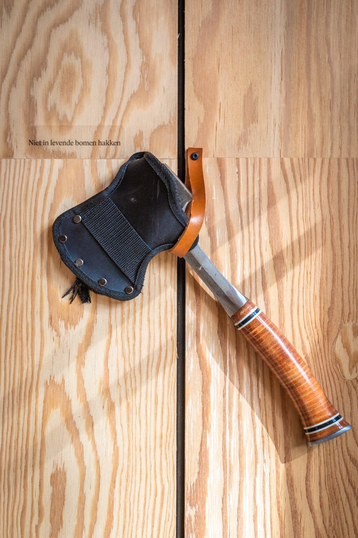 Bijl om hout mee te maken hangt aan een houten muur