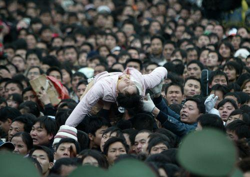 2008年1月31日、広州市にて1人の乗客が人混みの中で倒れ、乗客が頭越しに救出をする