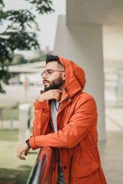 Millennial in an orange rain jacket trying to remember something