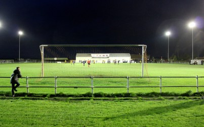 A lone spectator braves the strong winds behind the goal at Station Road, Norton.