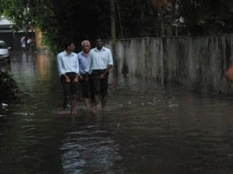 Staff from office walking through flooded lane.JPG