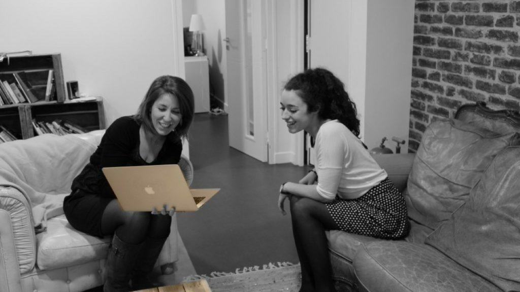 Deux personnes assis regardant un écran d'ordianateur portable