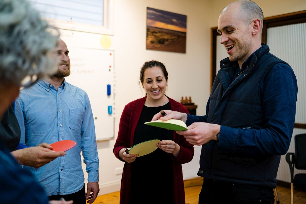 2 women and 2 men standing in a semicircle smiling or laughing. They are holding paper circles. Background has a whiteboard, wooden floor and sunset picture on the wall