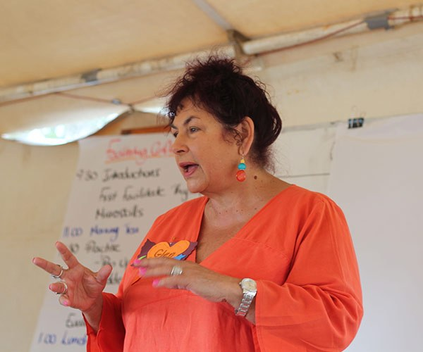 Woman Glen Ochre with hands gesturing and face alight facilitating a workshop