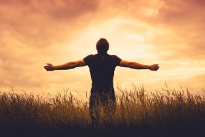 Discipleship Devotional Study Guide - Promises - Day 86 - Romans 8:26-27 - Helps Us In Our Weakness - Growing As Disciples of man standing in a field at sunset