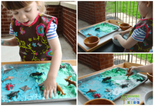 Earth day sensory play activity with shaving cream and miniature animals.