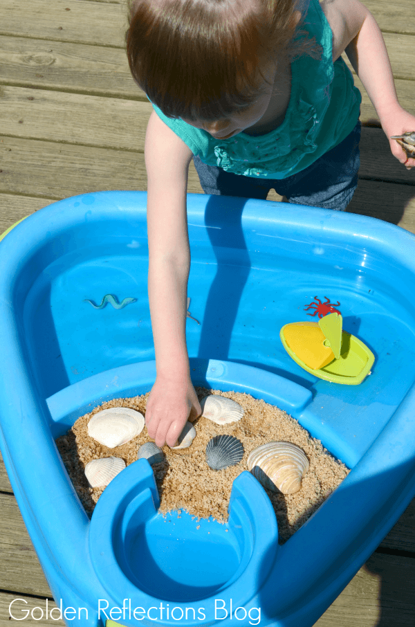 playing with beach themed water sensory table for toddlers