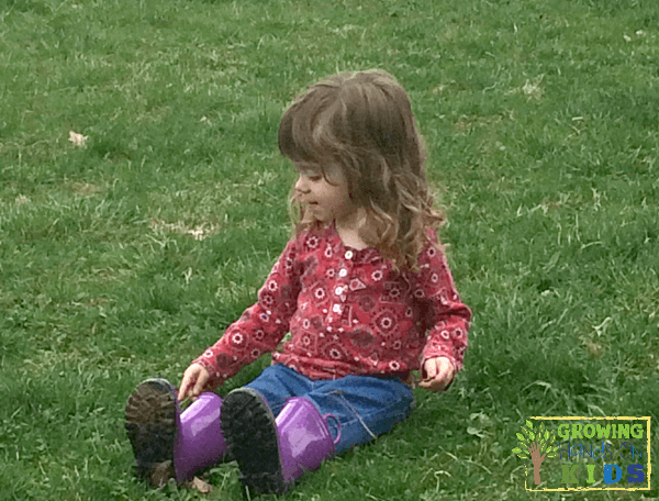 Child sitting and listening to nature sounds. Listening Scavenger Hunt for Kids.