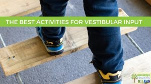 Child in blue pants and sneakers walking on a wood bridge. The words The Best Activities for Vestibular Input are written on the top of the graphic with a green background.