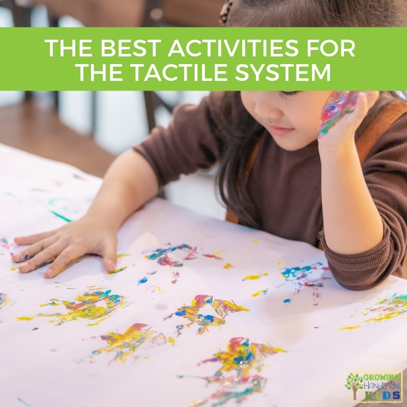 little girl finger painting on white paper. A green shaded box with the words The Best Activities for The Tactile System are at the top of the picture.
