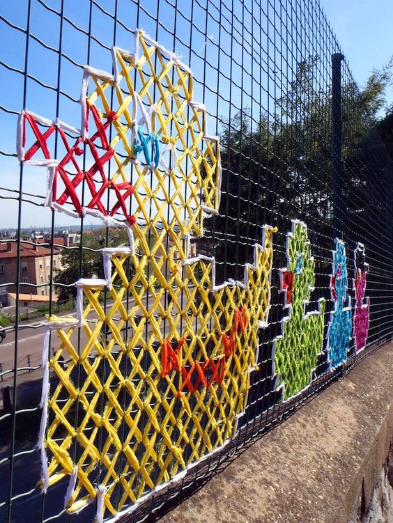 Brightening up a mesh fence with coloured cross stitch. Amazing.