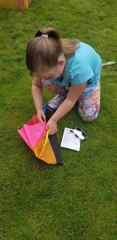 Girl unwrapping anpro kite for kids