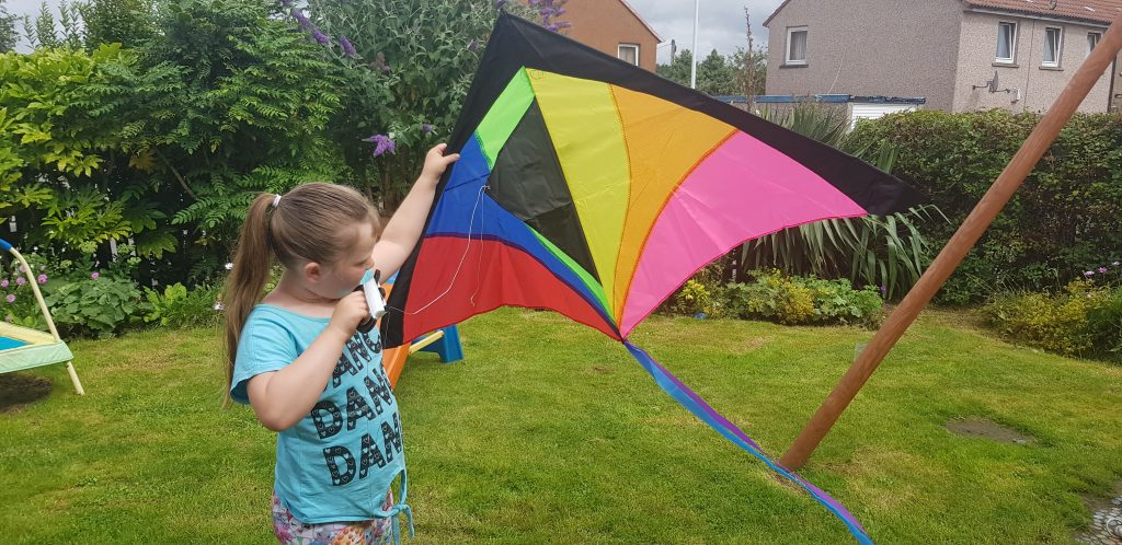Girl holding a finished rainbow kite up