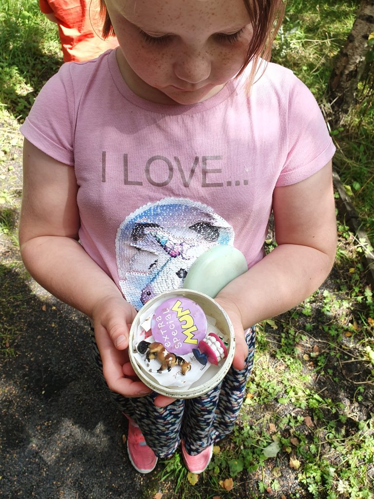 Geocache girl finding a cache of stuff
