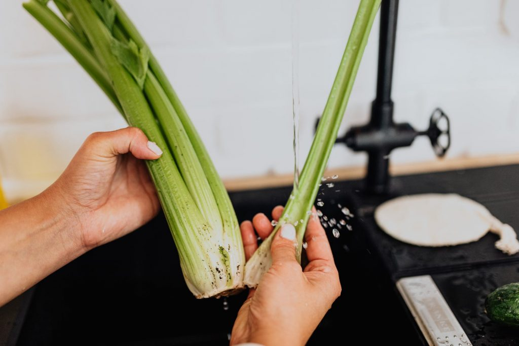 person holding and washing celery
