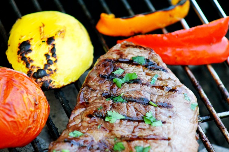 Steak on the grill with mango tomato and peppers onions