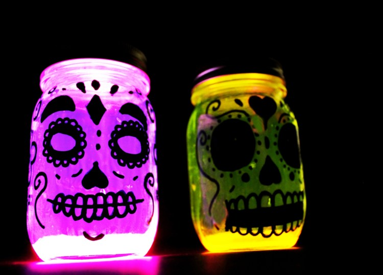 Glow in the dark Day of the Dead or Dia de los Muertos skull lanterns made with mason jars.