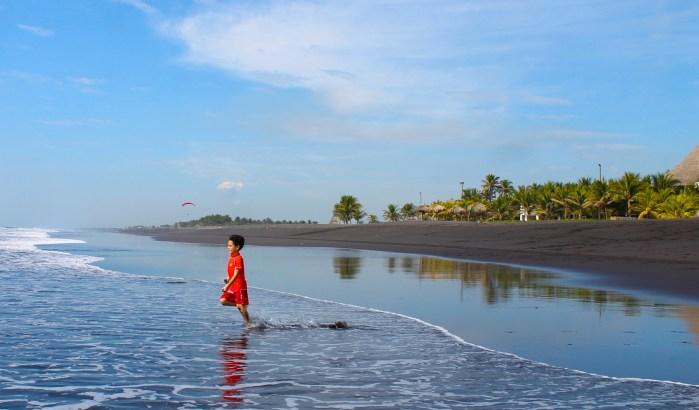 boy running in black san beach in Guatemala