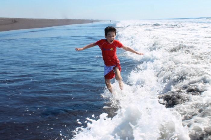 boy jumping waves in black sand beach in Guatemala